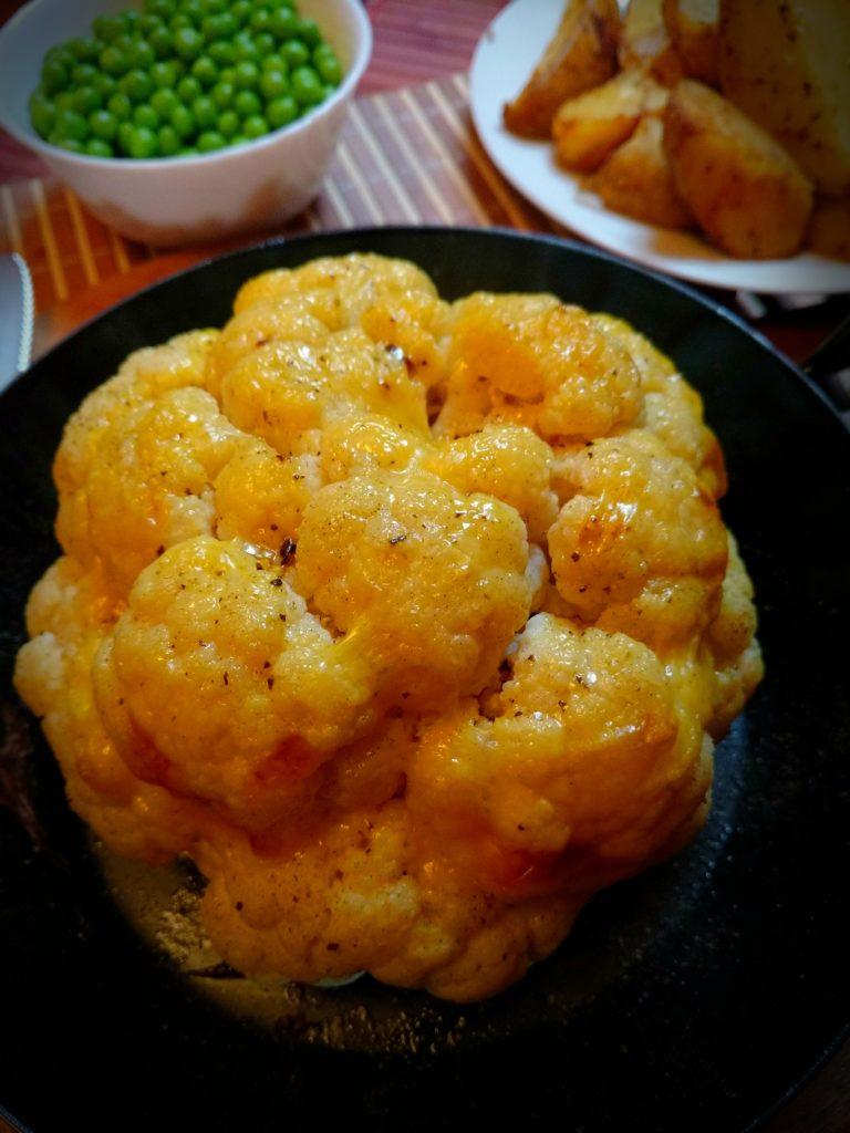 Im ganzen gebackener Butter-zarter Blumenkohl mit veganen Käsescheiben überbacken.