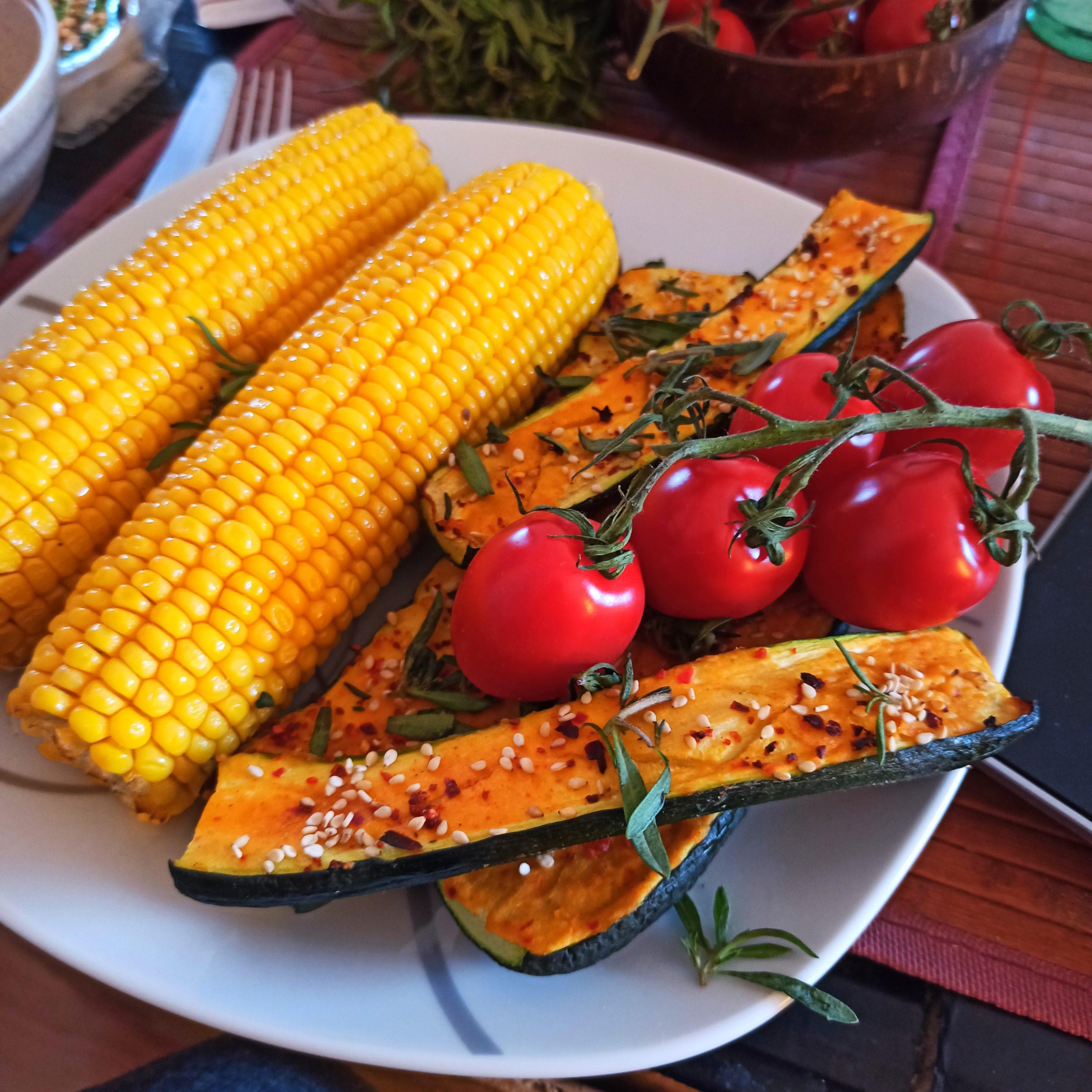 Gebackener Zuckermais und vegane mit Hummus überbackene Auberginen
